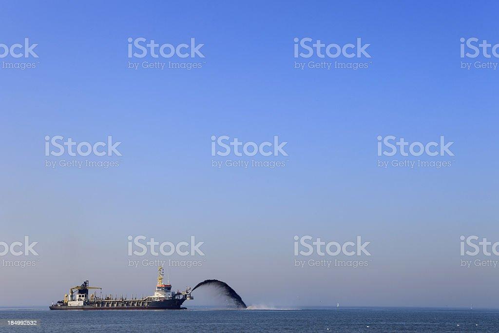dredger pumping sand onto the coastline stock photo