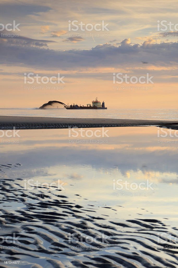 dredger pumping sand onto the coastline royalty-free stock photo