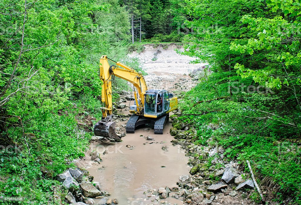 Dredger works in the trough of mountain stream. stock photo