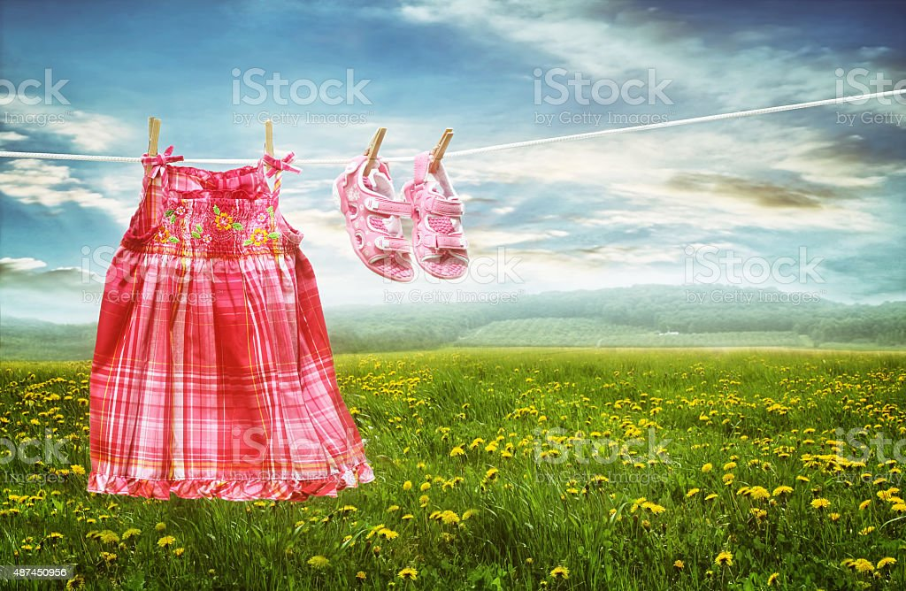 Dress and sandals on clothesline in fields of dandelions stock photo