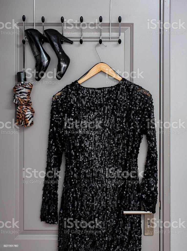 dress and shoes on a clothes rack inside door stock photo