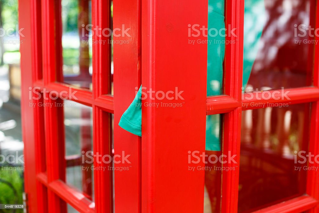 dress clamped door of red telephone box stock photo