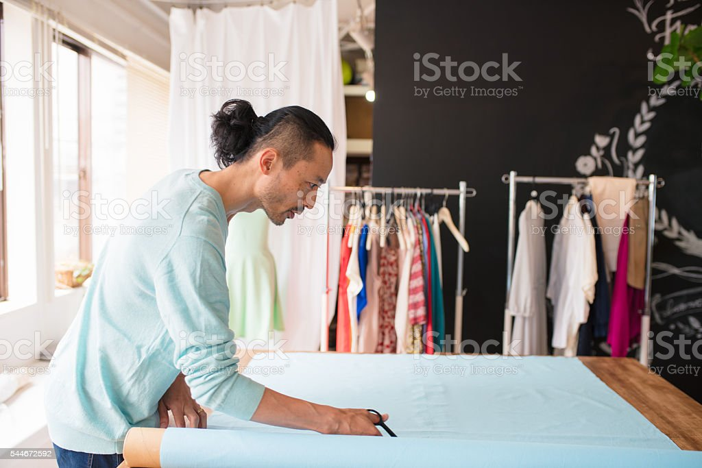 Dress maker cutting fabric stock photo