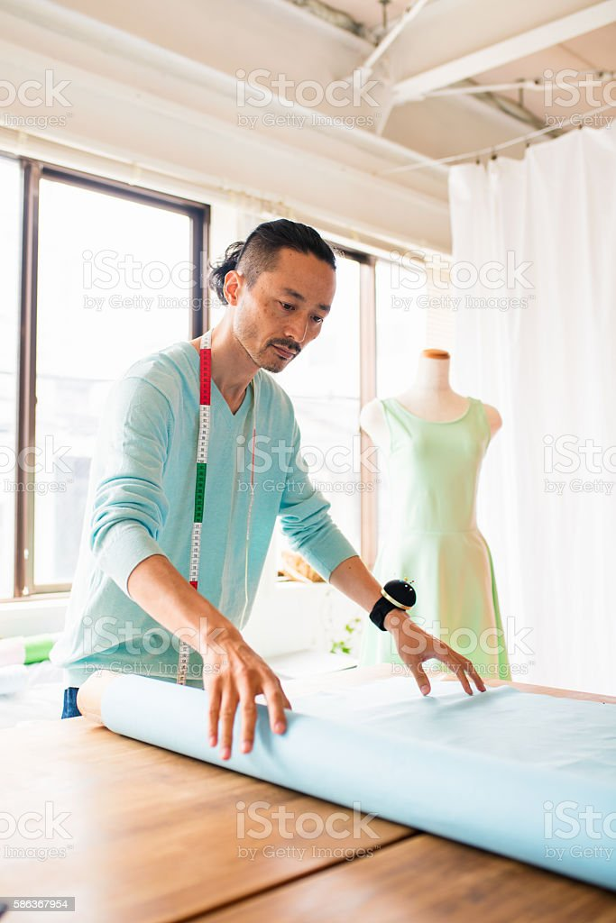 Dress maker rolling out fabric stock photo