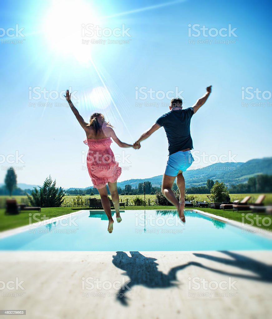 Dressed Couple Diving in Swimmingpool stock photo