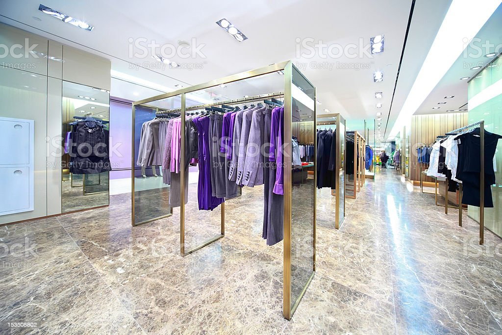 Dresses, blouses, jackets and suits in shop of female clothes stock photo