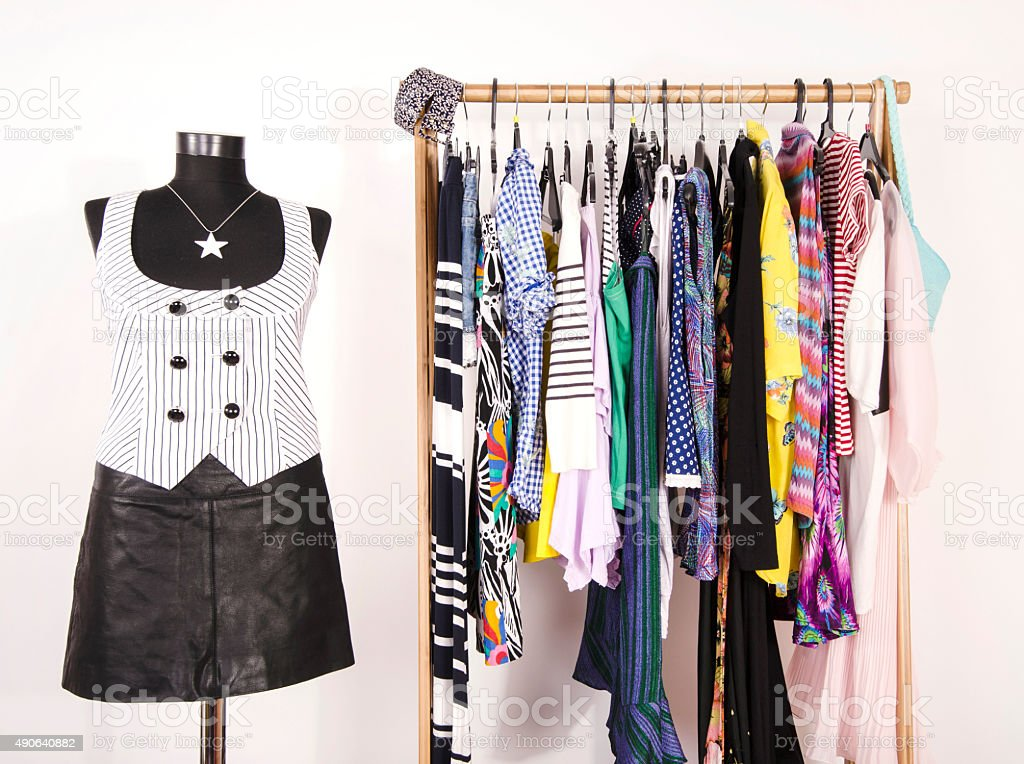 Dressing closet with colorful clothes arranged on hangers. stock photo
