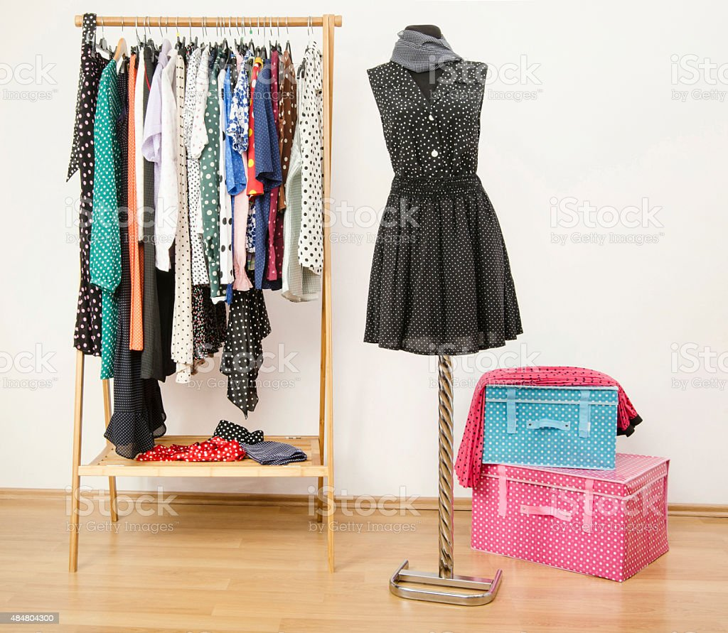 Dressing closet with polka dots clothes arranged on hangers. stock photo