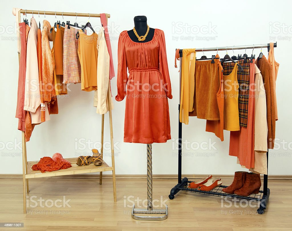 Dressing closet with shades of orange clothes, shoes and accessories. stock photo