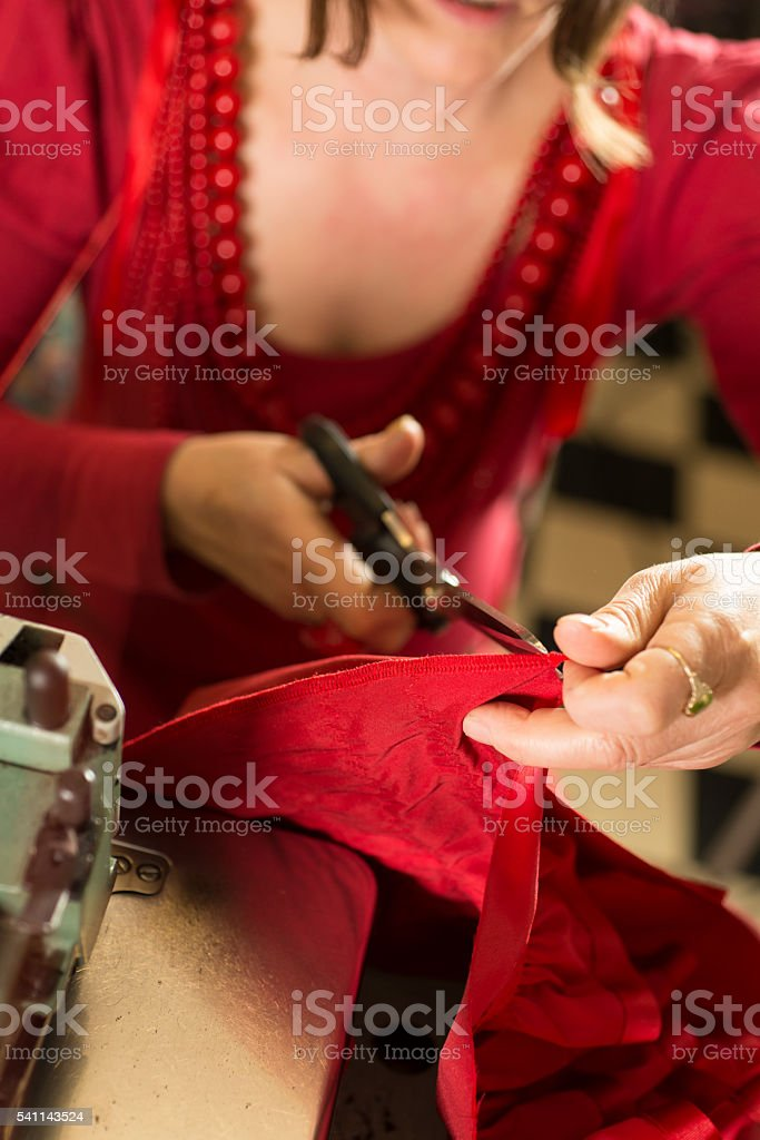 Dressmaker Cutting Cloth with Tailor Shears stock photo
