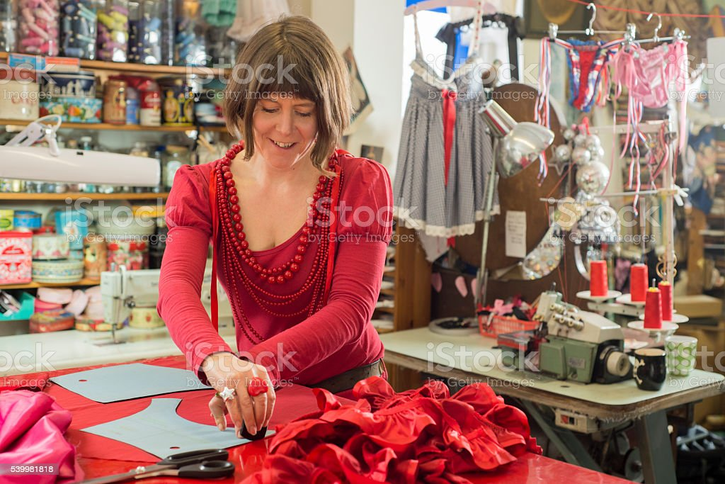 Dressmaker in Red Dress and Necklaces Happily Tracing Cloth stock photo
