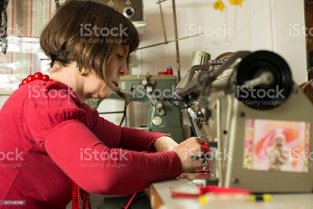 Dressmaker Stitiching Fabric Through Sewing Machine stock photo
