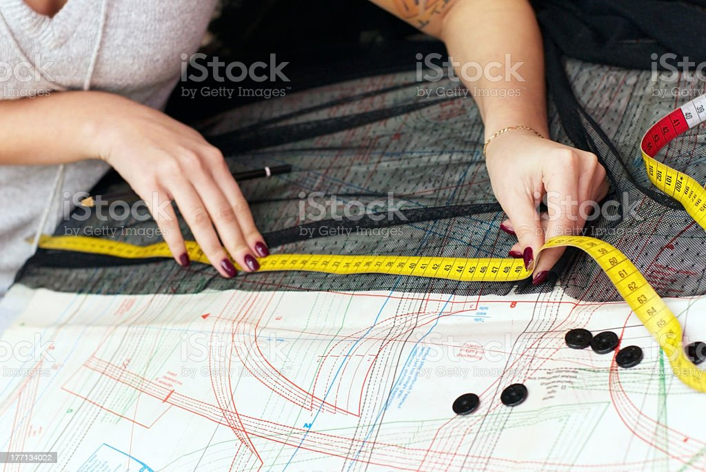 A dressmaker using a measuring tape on a cloth stock photo