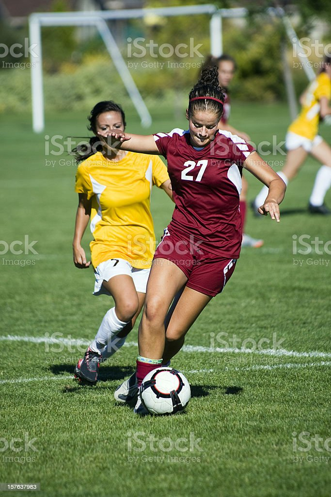 Dribbling Female Soccer Player Breaks Away From Defense royalty-free stock photo
