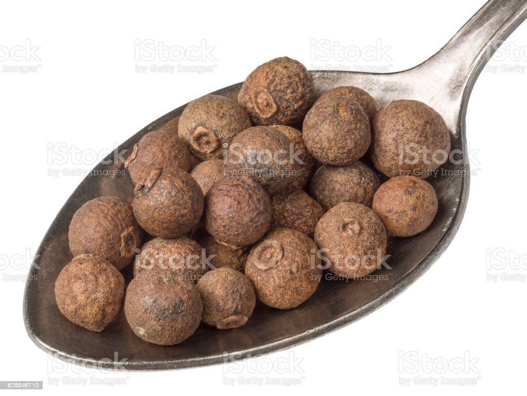 Dried allspice english pepper berries on silver spoon isolated on white. stock photo