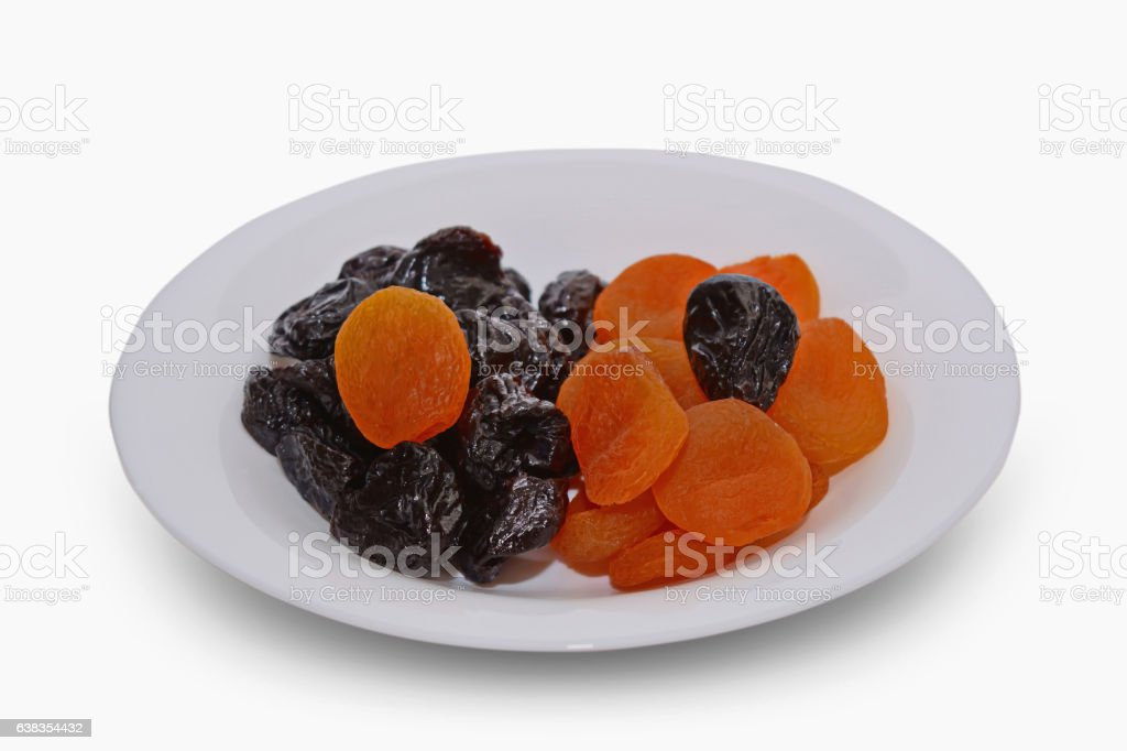 Dried apricots and prunes on a white background. stock photo
