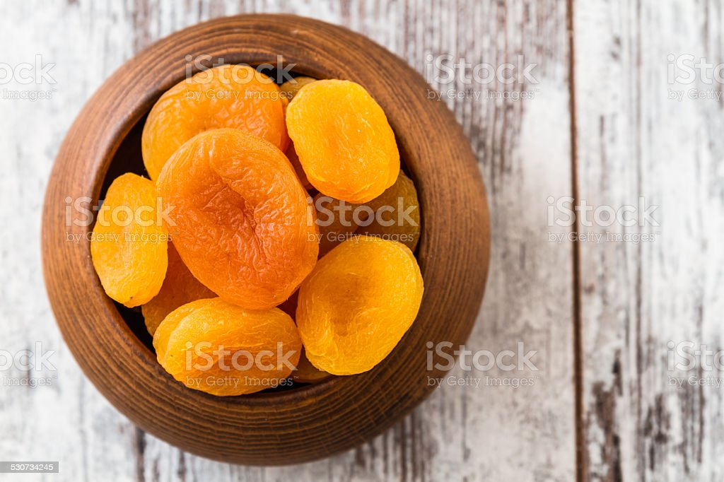 Dried Apricots in Wooden Bowl stock photo