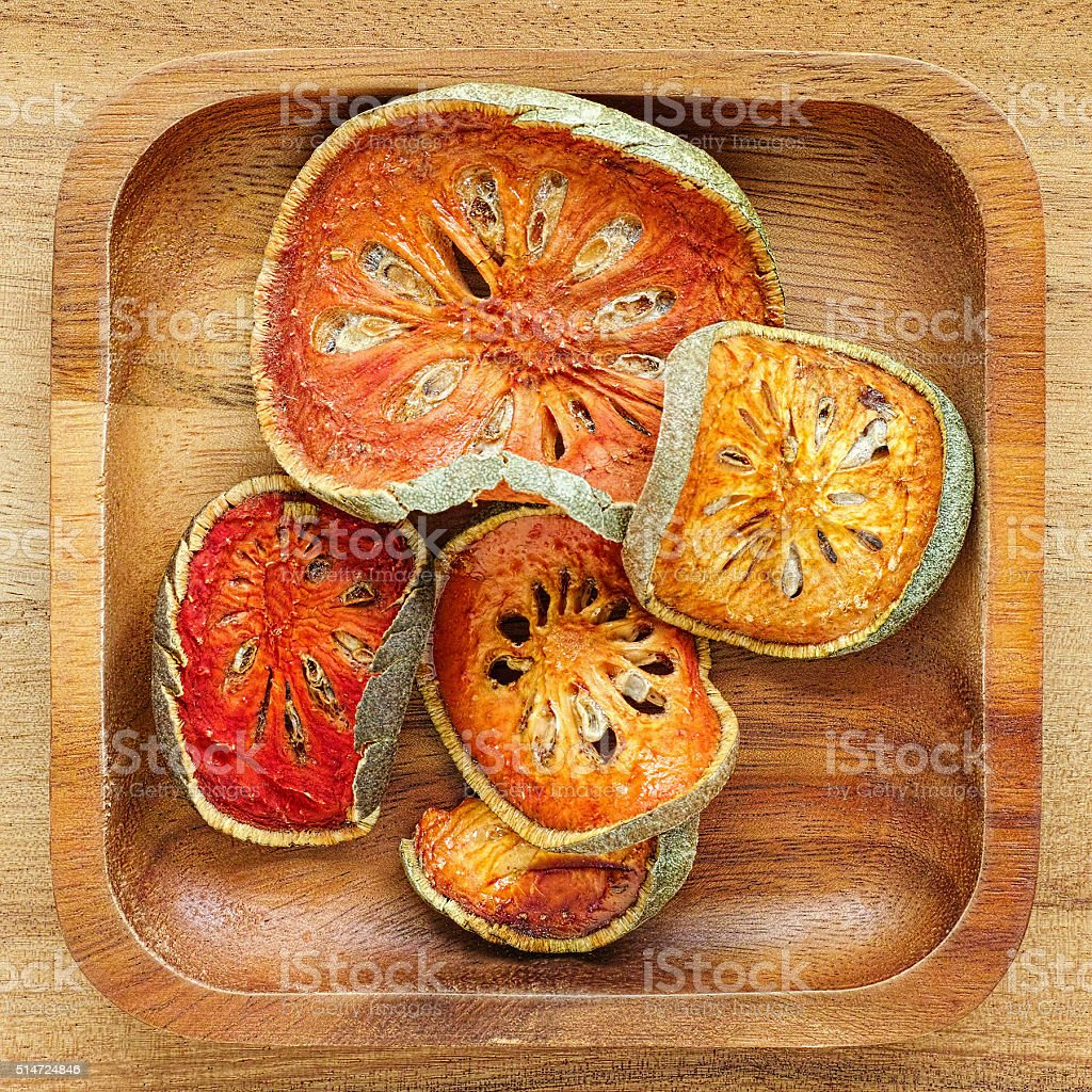 Dried Bael fruit in a wooden tray. stock photo