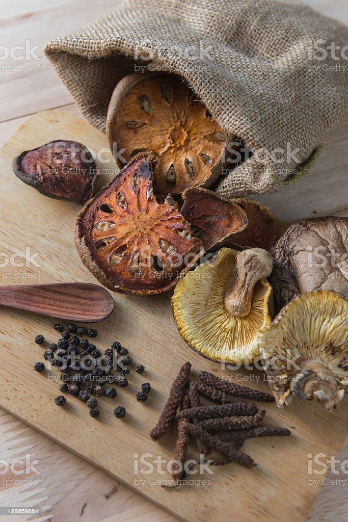 Dried balefruit,long pepper,black pepper,mushroom) on wooden background. stock photo