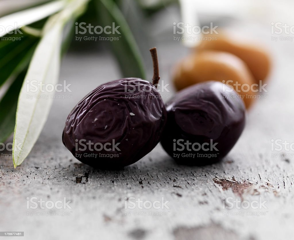 Dried black olives on floor with leaves royalty-free stock photo