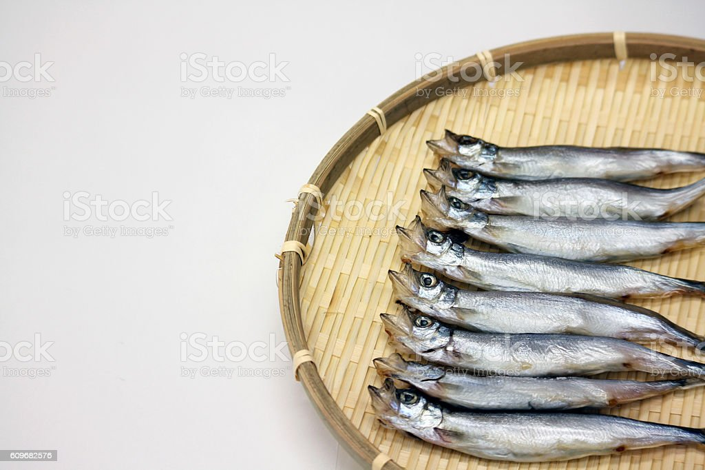 Dried Capelin fish on bamboo tray in white background in stock photo