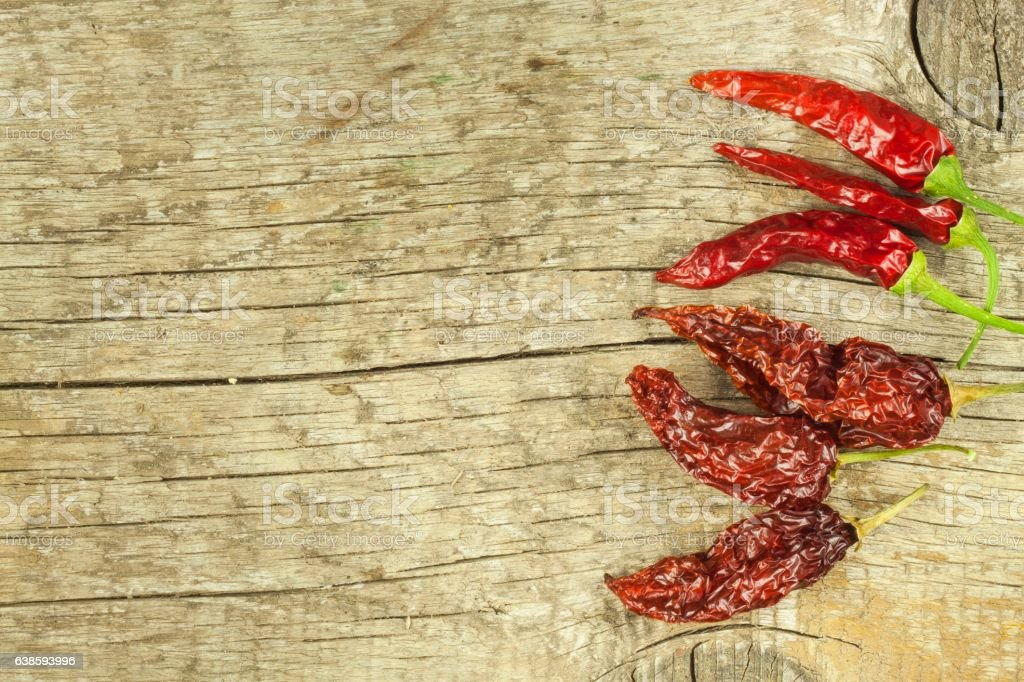 Dried chili peppers on old wooden background. stock photo