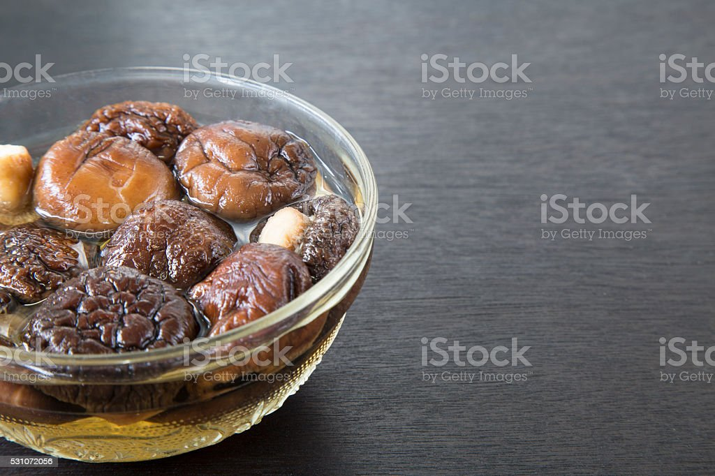 Dried Chinese mushroom in water on black wooden background. stock photo