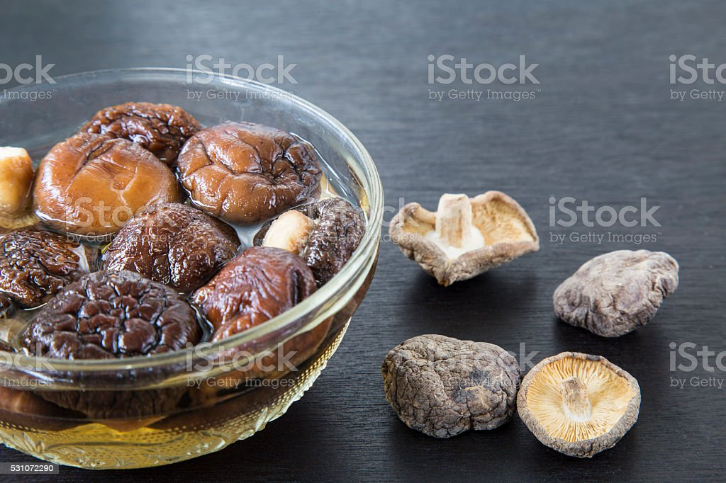 Dried Chinese mushroom on black wooden background. stock photo