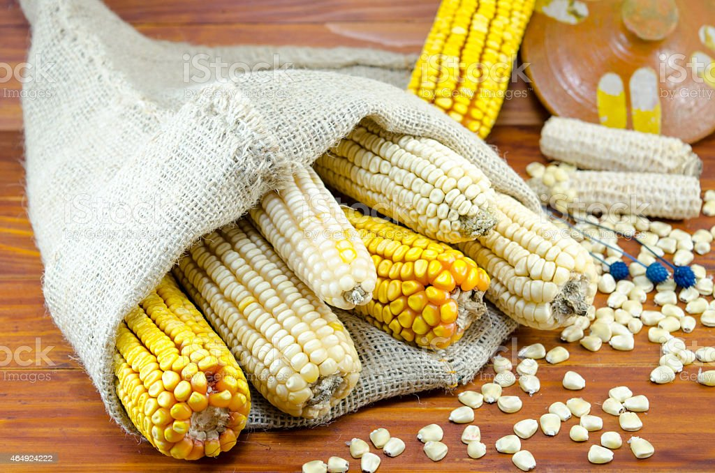 Dried corn cobs in a bag on a wooden table royalty-free stock photo