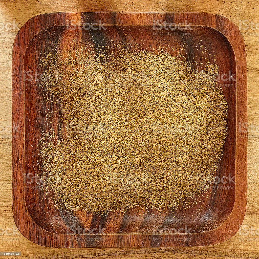Dried Cumin powder in a wooden tray. stock photo