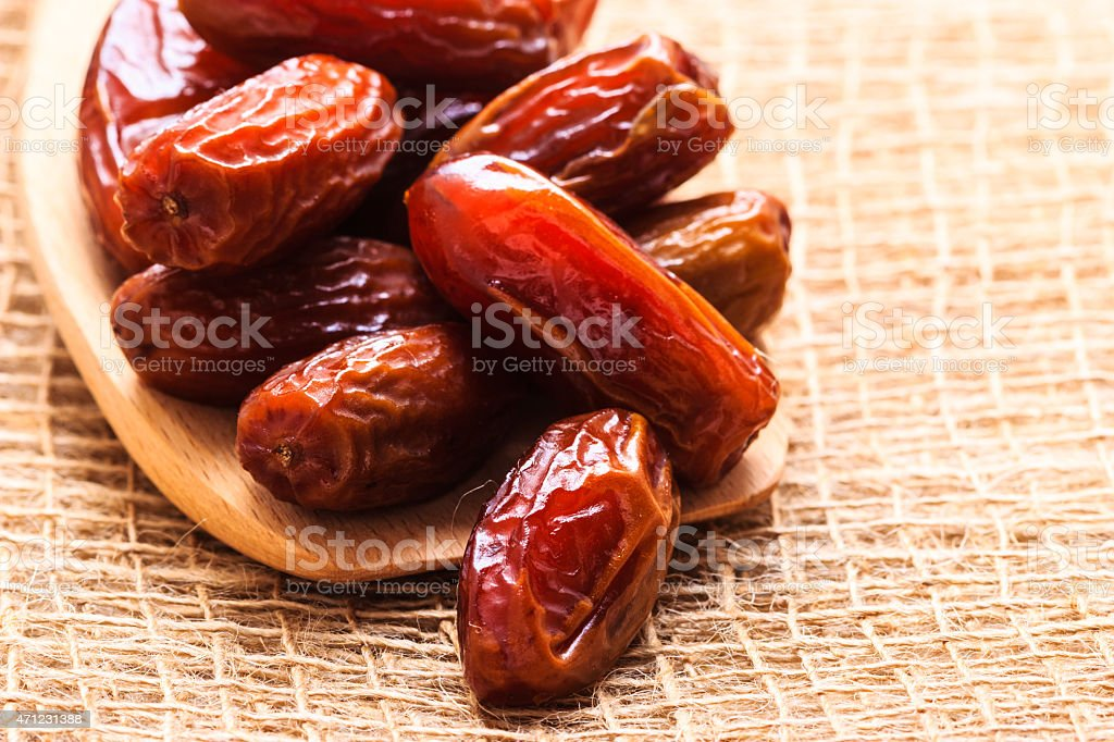 dried dates on wooden spoon cloth background stock photo