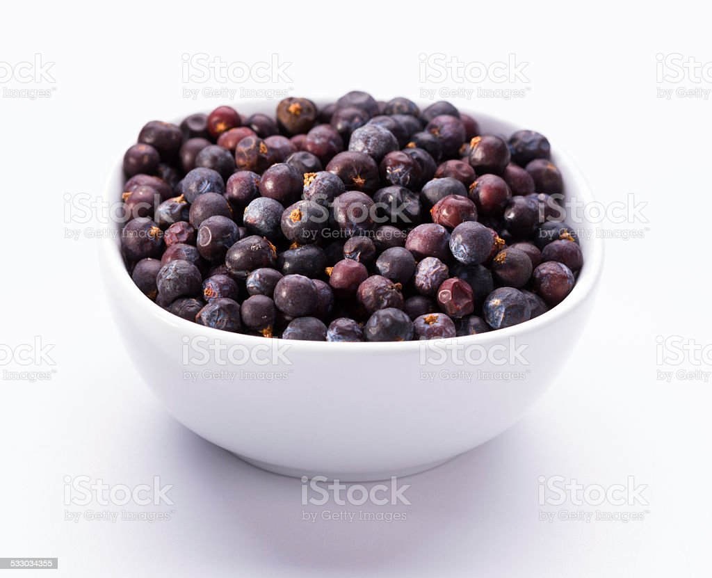 dried elderberries in small white bowl stock photo