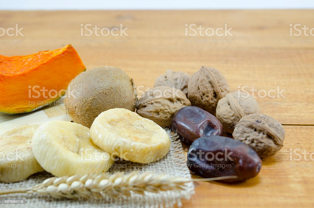 Dried figs, palms, pumpkins, wheat with walnuts and kiwis royalty-free stock photo