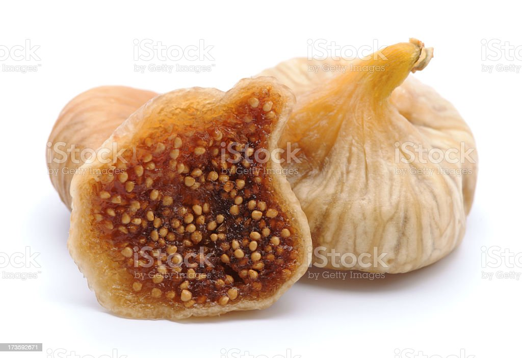 Dried figs with one chopped in half isolated on white stock photo
