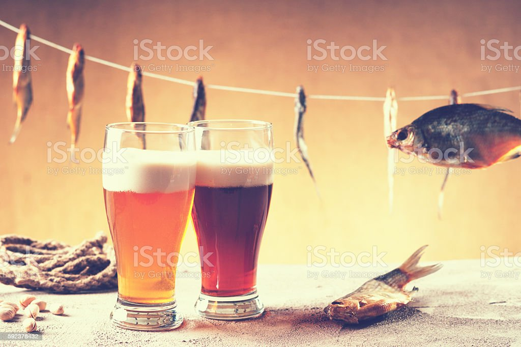 Dried fish, rope, pistachio nuts and beer stock photo