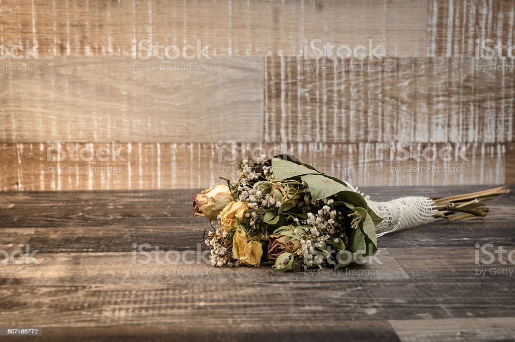 Dried flower bouquet with beautiful roses on a rustic old wooden...