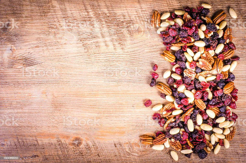 Dried fruits - pecan, cranberry, raisin, almond on wooden stock photo