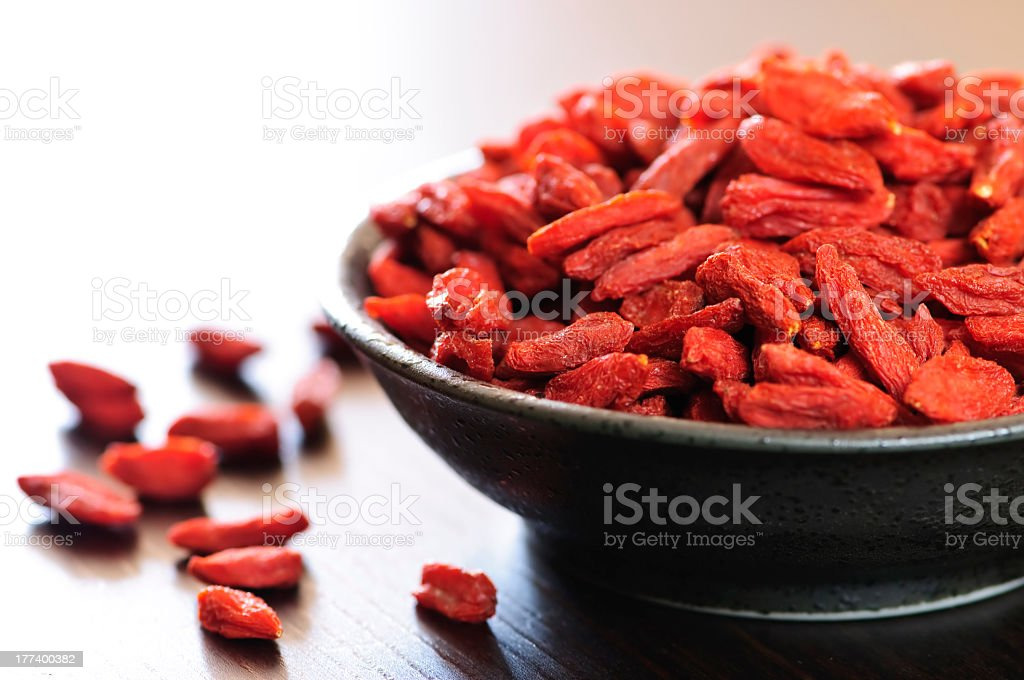 Dried goji berries in a dark bowl stock photo