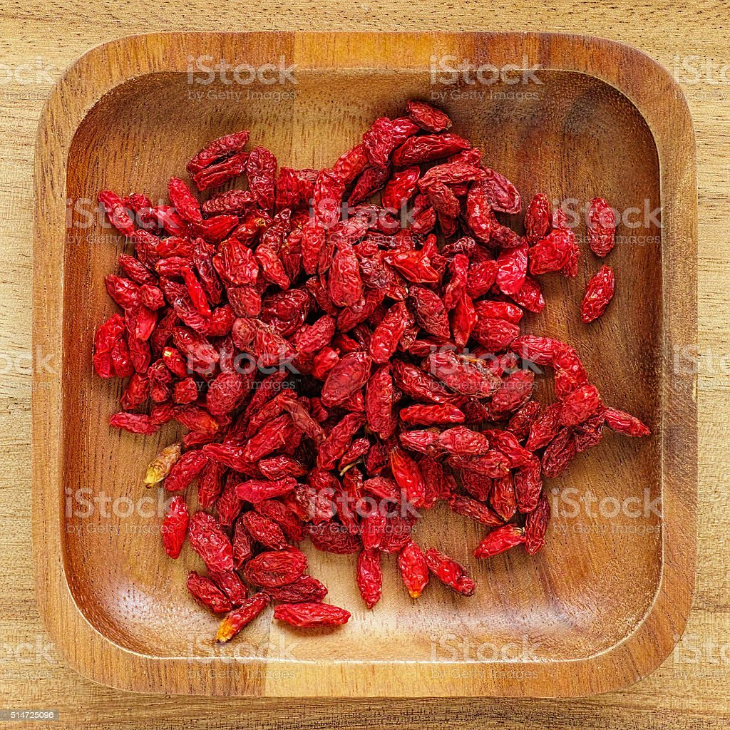 Dried Goji berries in a wooden tray. stock photo