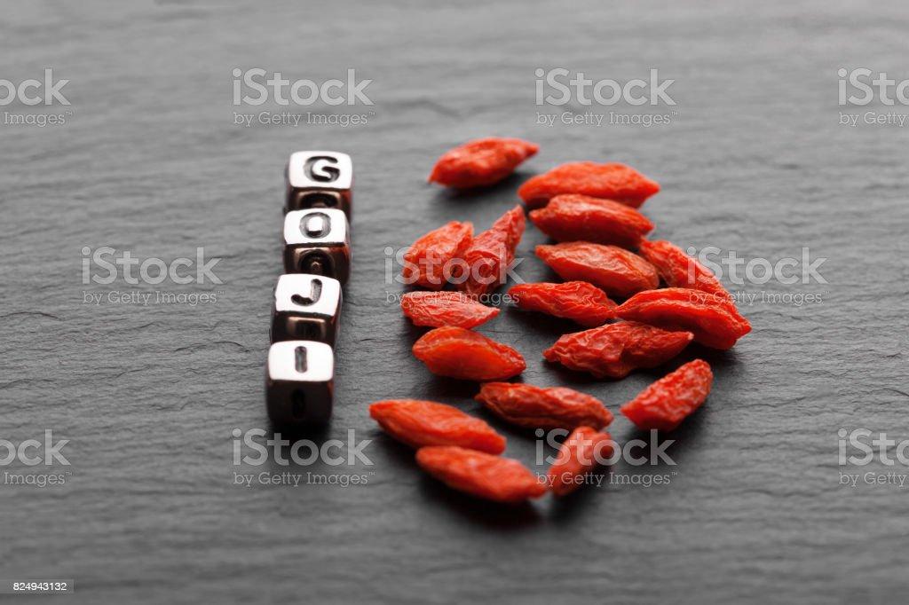 Dried goji berries on black wooden background stock photo