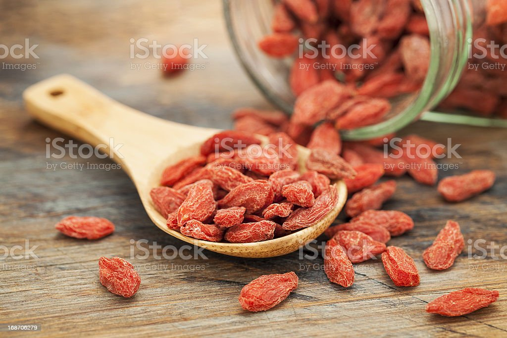 Dried goji berries poured on a wooden spoon from glass jar stock photo