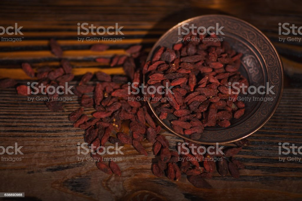 Dried Goji in a metalic bowl on wooden background stock photo
