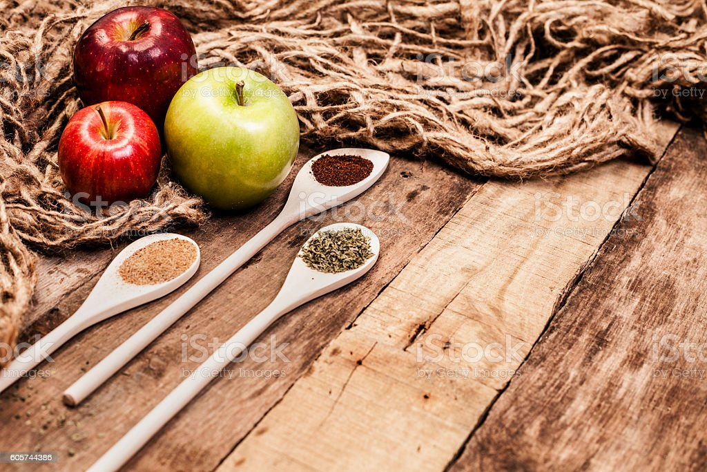 Dried herbs and spices with apples on rustic wooden table. stock photo