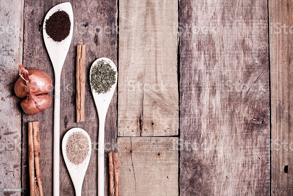 Dried herbs and spices with shallots on rustic wooden table. stock photo