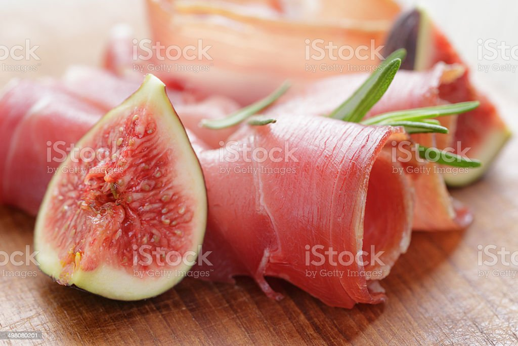 dried jamon slices with figs on wood table stock photo