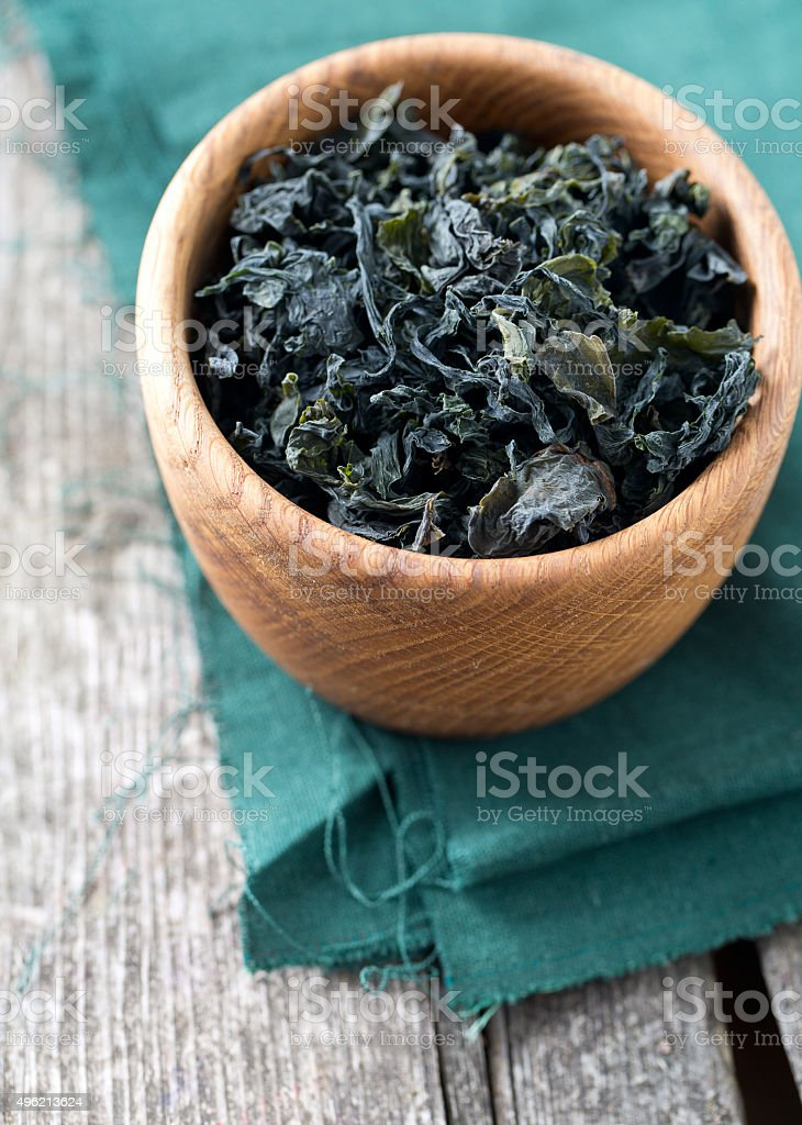 dried laminaria in a bowl on wooden surface stock photo