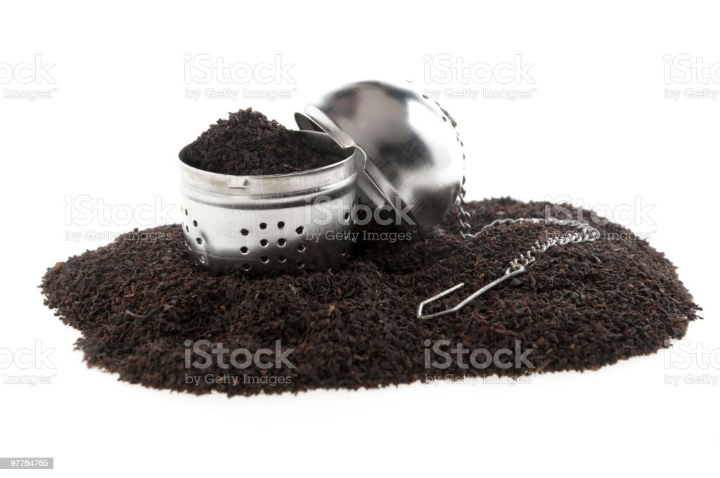 dried leaves of tea and  filter infuser stock photo