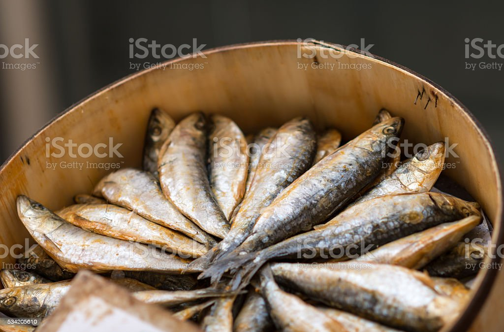 dried mackerel on a market at a wooden basket stock photo