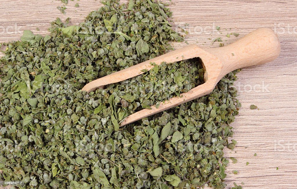 Dried marjoram with spoon on wooden background stock photo