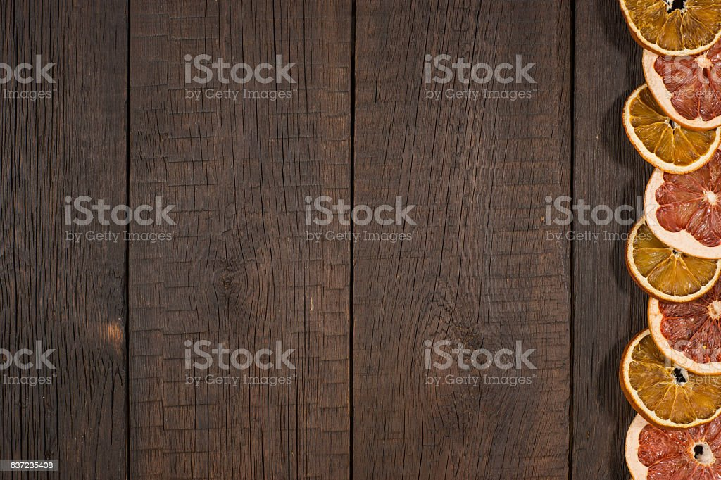 Dried oranges and grapefruits in the old dark wood table. stock photo